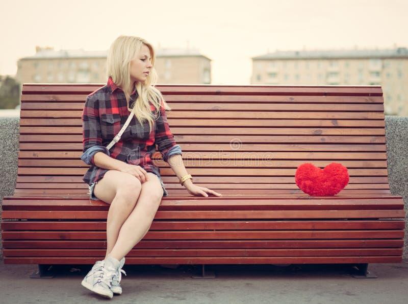 Smutny osamotniony dziewczyny obsiadanie na ławce blisko duży czerwony serce zdjęcie stock