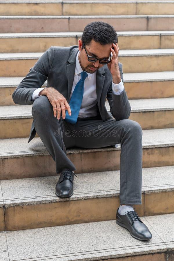 Smutny przyglądający młody biznesmena obsiadanie przy schody obraz stock