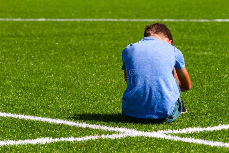 Smutny rozczarowany ch?opiec obsiadanie na trawie w stadium obrazy royalty free