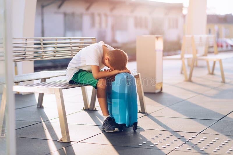 Smutny samotny chłopiec dziecko czeka samotnie z jego bagażem obrazy stock