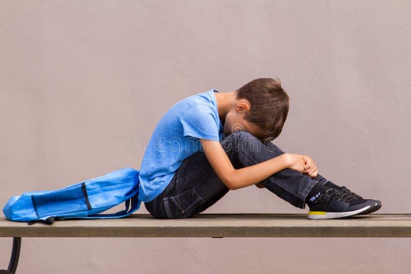 Smutny samotny dziecka obsiadanie na ławce outdoors obraz stock