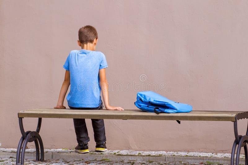 Smutny samotny dziecka obsiadanie na ławce outdoors obraz royalty free