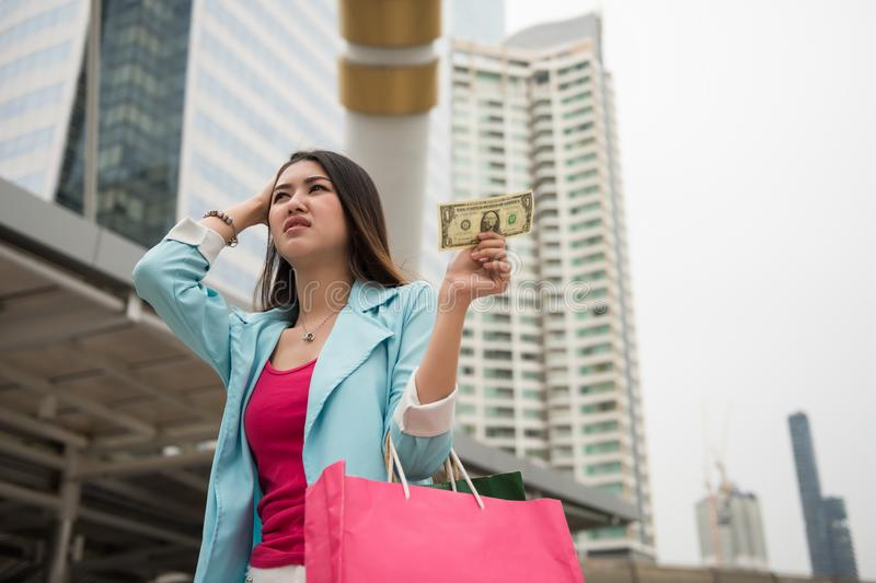 Smutny shopaholic dziewczyna chwyt jeden dolar zdjęcia royalty free