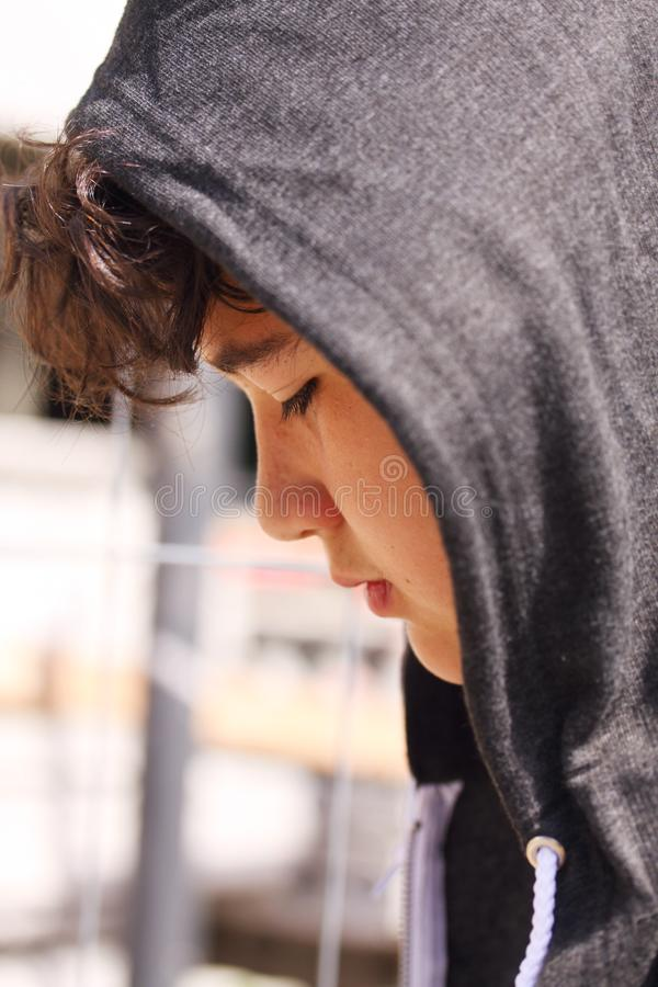 Smutny skołatany latynosa 13 lat szkolnej chłopiec nastolatek jest ubranym hoodie pozować plenerowy - zakończenie up zdjęcia stock