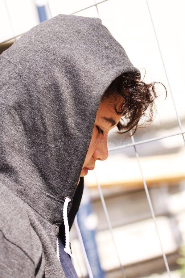 Smutny skołatany latynosa 13 lat szkolnej chłopiec nastolatek jest ubranym hoodie pozować plenerowy - zakończenie up zdjęcia royalty free