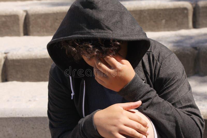 Smutny skołatany latynosa 13 lat szkolny nastolatek pozuje plenerowego obsiadanie na ulicie - zakończenie up obraz stock
