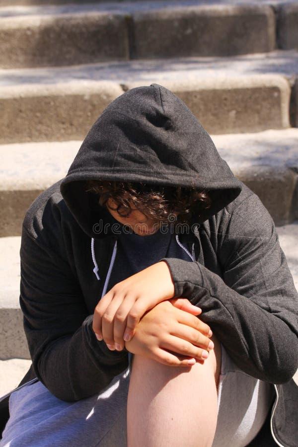 Smutny skołatany latynosa 13 lat szkolny nastolatek pozuje plenerowego obsiadanie na ulicie - zakończenie up zdjęcia stock