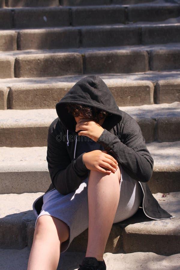 Smutny skołatany latynosa 13 lat szkolny nastolatek pozuje plenerowego obsiadanie na ulicie - zamyka up twarz fotografia stock