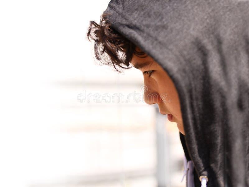 Smutny skołatany szkolnej chłopiec nastolatek jest ubranym hoodie pozuje i myśleć w jego swój myślach - zamyka w górę akcyjnej fo obrazy stock