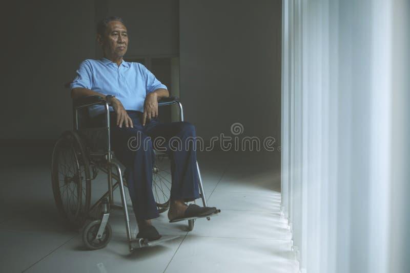 Smutny starego człowieka obsiadanie w wózku inwalidzkim obraz stock