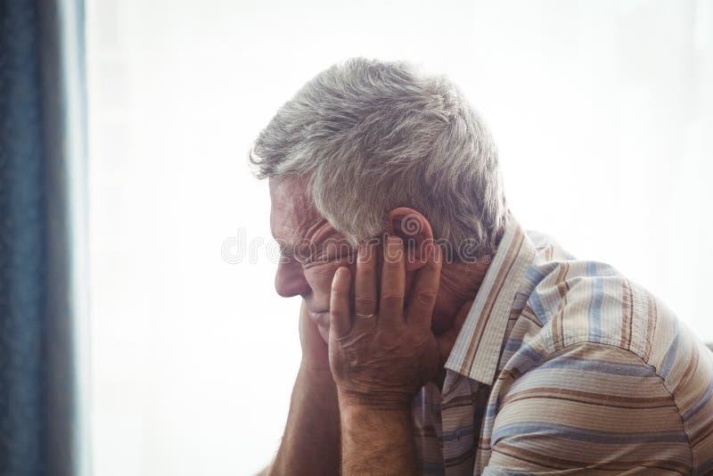 Smutny starszego mężczyzna obsiadanie zdjęcie stock