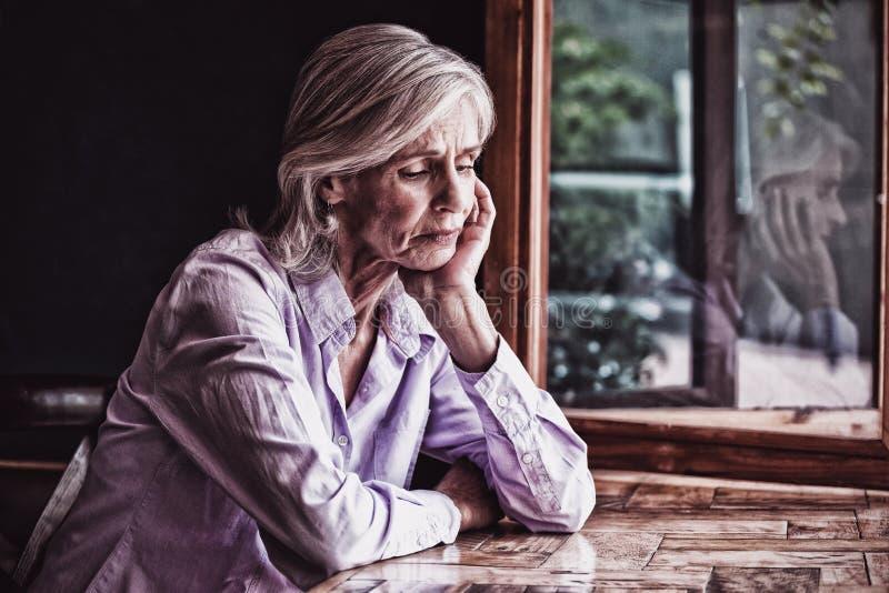 Smutny starszy kobiety obsiadanie przy stołem obraz royalty free
