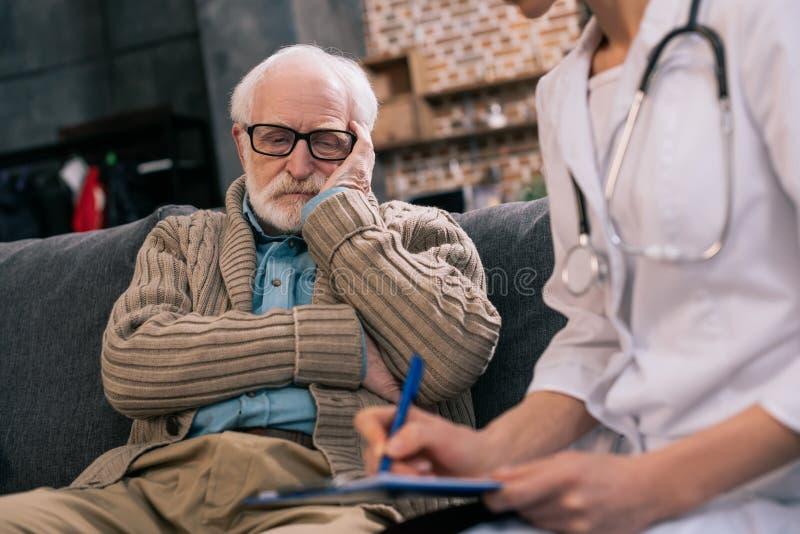 Smutny starszy mężczyzna patrzeje doktorskiego pisze puszek zdjęcia stock