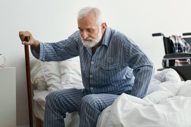 Smutny starszy mężczyzna z chorobą Alzheimera trzymający laskę i siedzący na łóżku w domu opieki obraz royalty free