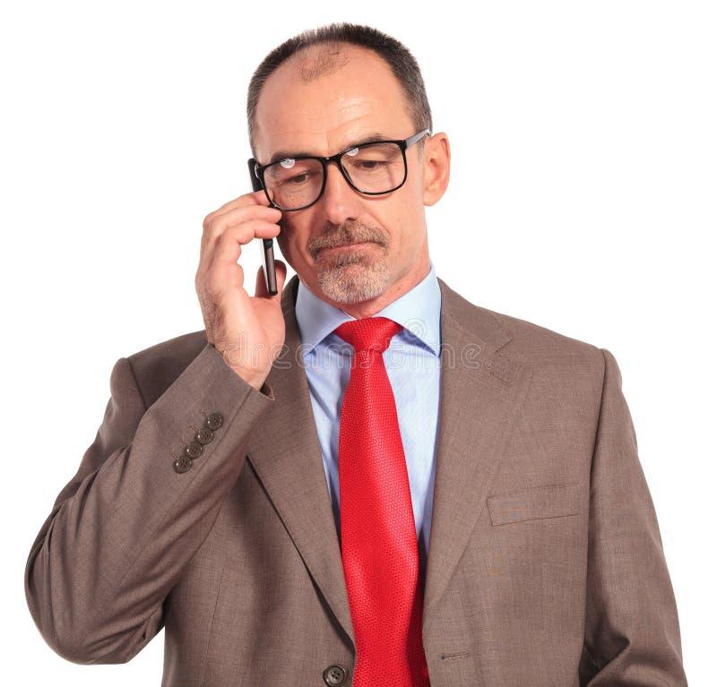 Smutny stary biznesmen opowiada na telefonie obrazy royalty free