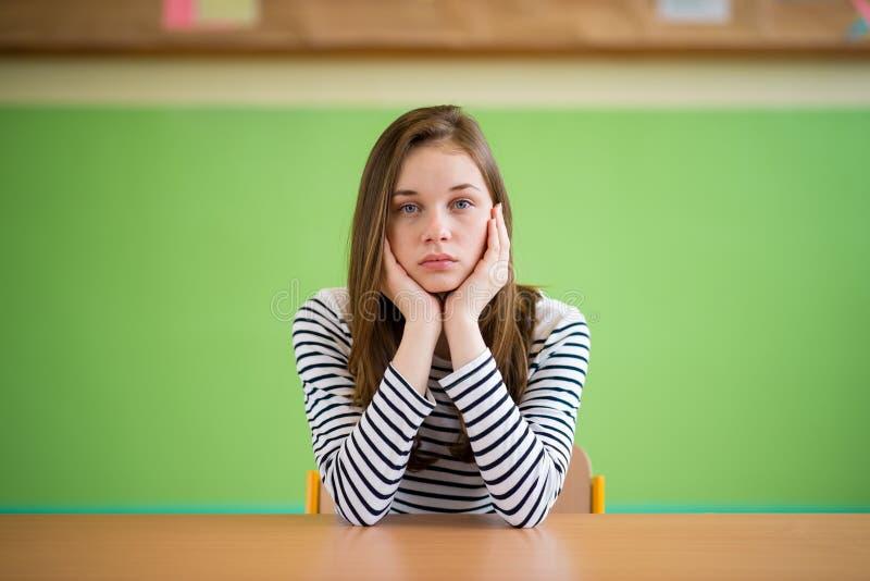 Smutny studencki obsiadanie w sala lekcyjnej z jej głową w rękach Edukacja, szkoła średnia, znęcać się, nacisk, depresja obraz royalty free