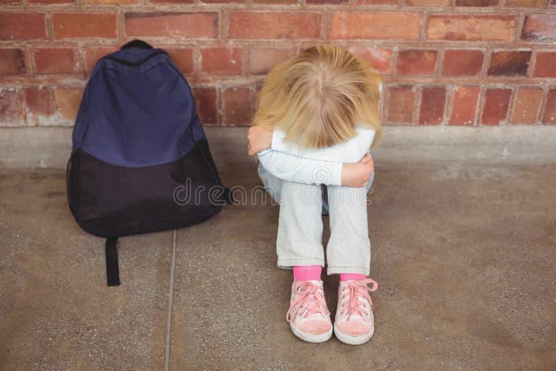 Smutny uczeń siedzi samotnie na ziemi zdjęcie stock