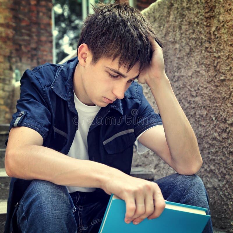 Smutny uczeń z książką obrazy royalty free