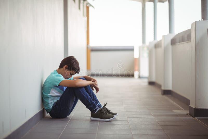 Smutny uczniowski obsiadanie w korytarzu zdjęcie royalty free