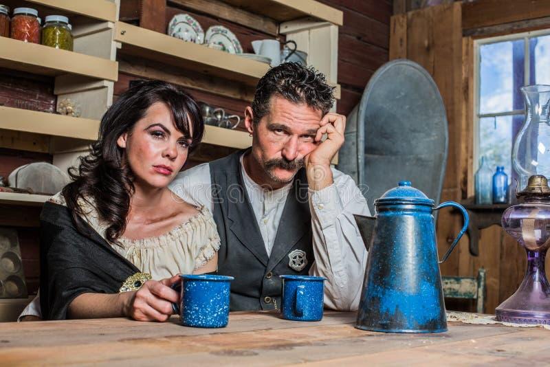 Smutny Zachodni szeryfa i kobiety pozy Inside dom zdjęcia stock