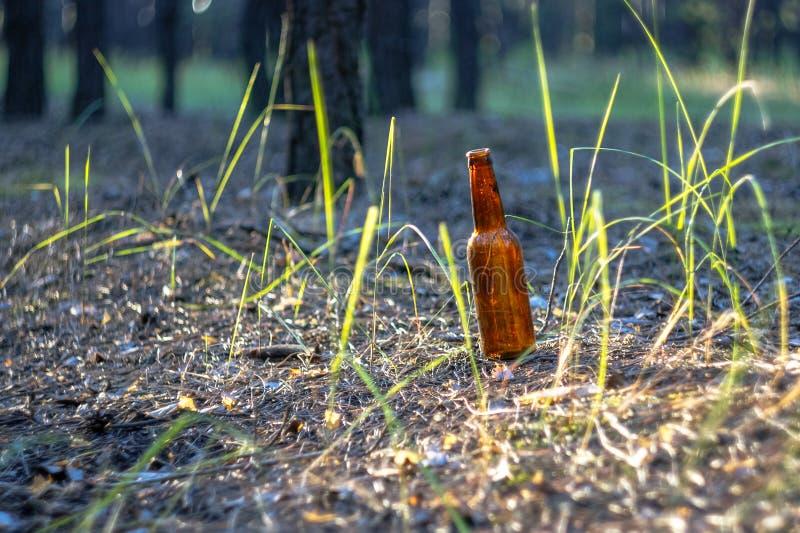 Smutsa ner den bruna ölflaskan på jordningen royaltyfri bild