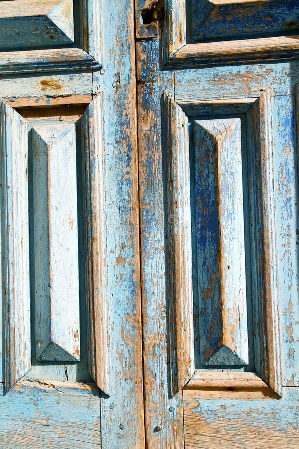 smutsa ner målarfärg i den rostiga blåa dörren spikar royaltyfria foton