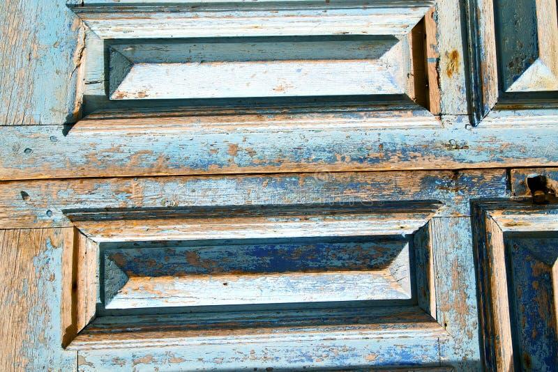 Smutsa ner målarfärg som den rostiga blåa dörren spikar royaltyfria foton