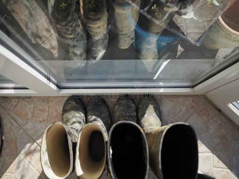 Smutsa ner welly kängor vid drivhusfönstret arkivfoto