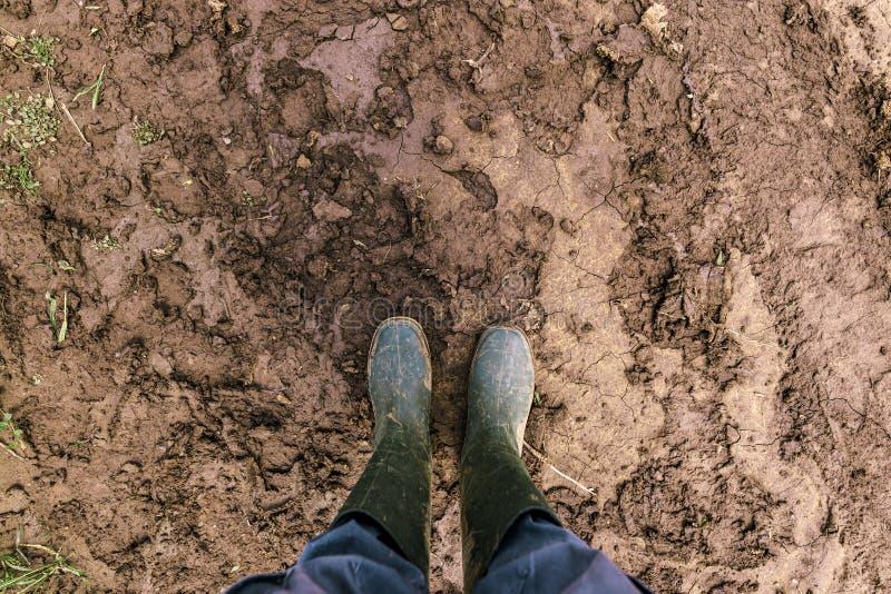 Smutsig bondes gummistöveler på den leriga landsvägen royaltyfri fotografi