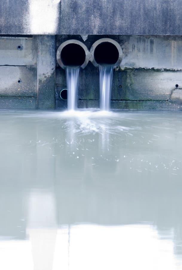Smutsig drain som förorenar en flod arkivfoton