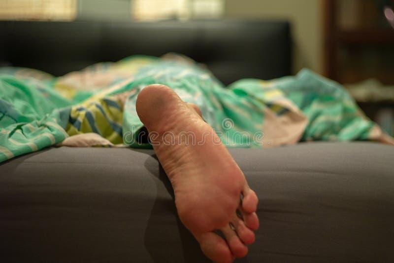 Smutsig fot för Closeup av mannen som sover på sängen i sovrum, når att ha arbetat hårt hela dagen royaltyfria bilder