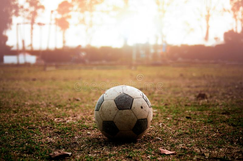 Smutsig fotboll på solnedgången royaltyfria bilder