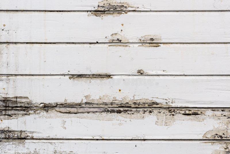 Smutsig gammal riden ut vit utanför träplankaväggen royaltyfria foton