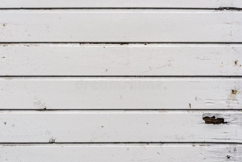 Smutsig gammal riden ut vit utanför träplankaväggen arkivfoto