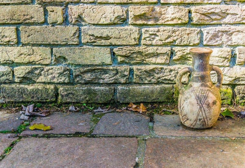 Smutsig gul tegelstenvägg med en gammal historisk seende textur för urna- och stentrottoarbakgrund arkivfoton