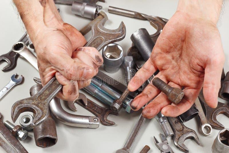 Smutsig hand av militären med hjälpmedel för att reparera maskiner i seminarium arkivbild