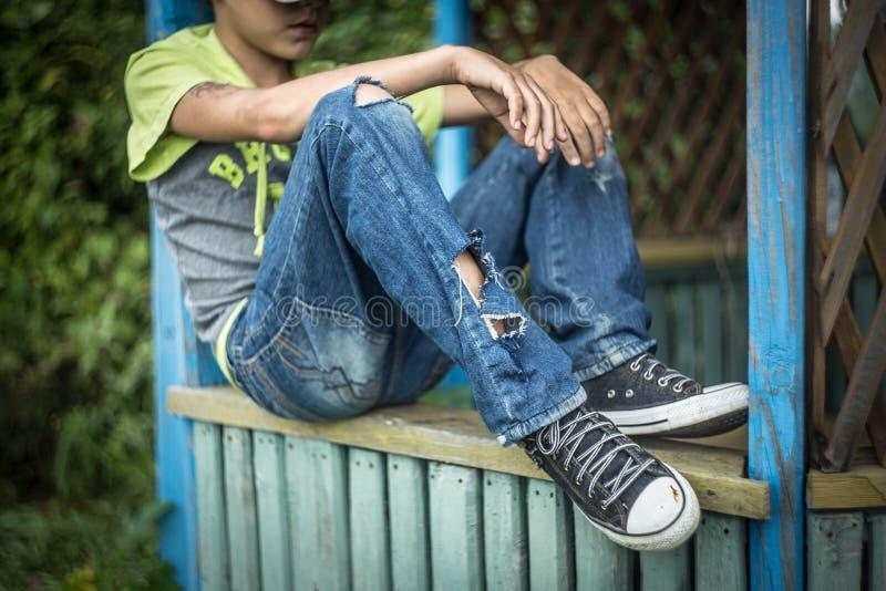 Smutsig hemlös pojke för foto med sönderriven jeans fotografering för bildbyråer