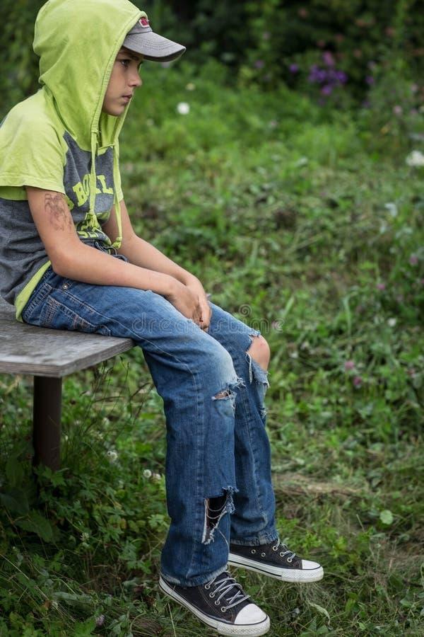 Smutsig hemlös pojke för foto med sönderriven jeans arkivfoto