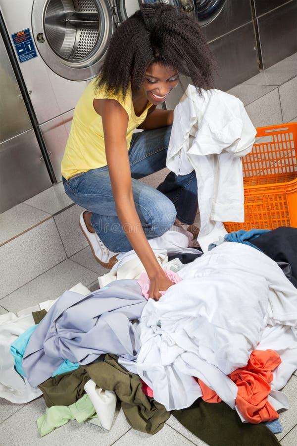 Smutsig kläder för kvinnaplockning på tvätterit royaltyfria foton