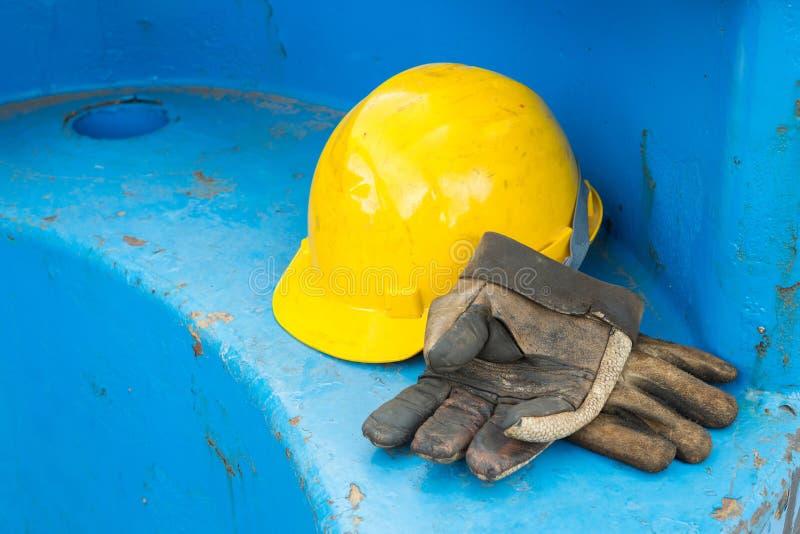 Smutsig läderhandskar och säkerhetshjälm arkivbild