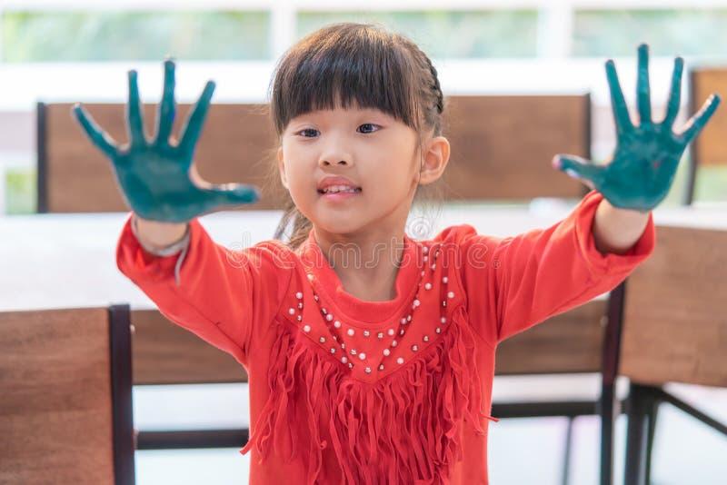 Smutsig målad hand för unge i konstklassrum arkivbilder