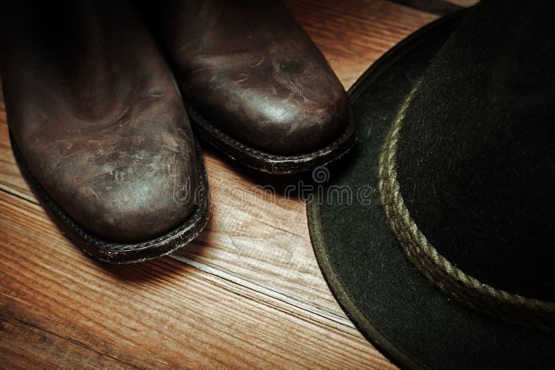 Smutsig och använd brun botts för västra rodeocowboy och hatt fotografering för bildbyråer