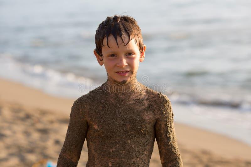 Smutsig pojkeunge för våt sand som ler, medan spela på stranden Varm solnedgånglampa Familjsommarloppet semestrar på havet eller  arkivfoton