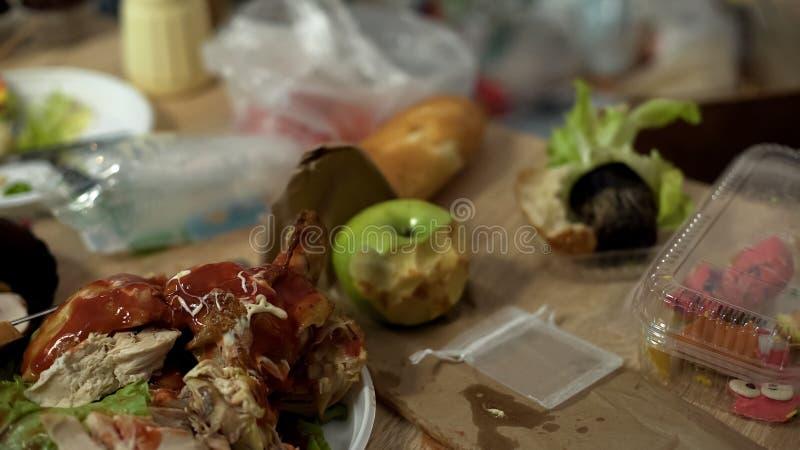 Smutsig tabell med smutsiga plattor som är fulla av fettiga sjukliga matrester, smutsigt rum arkivfoto