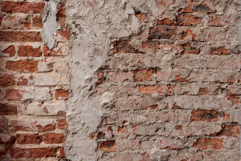 Smutsig tegelstenvägg för gammal tappning med skalning av murbruk, bakgrund, texturslut upp Sjaskig byggnadsfasad med skadad murb royaltyfria bilder