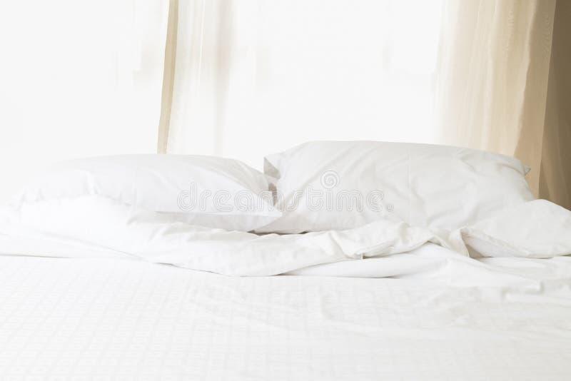 Smutsig vit säng med kudde- och filtmorgonsolljus igenom royaltyfri foto