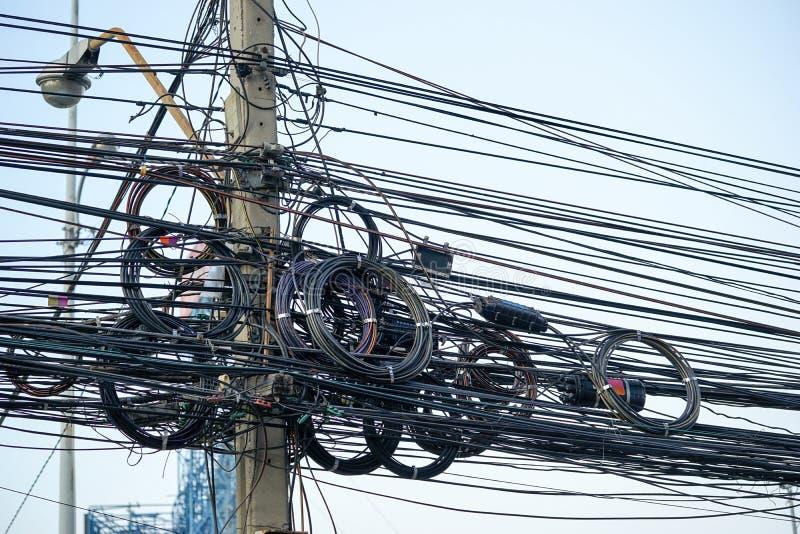 Smutsiga elektriska kablar och trådar på elektrisk pol arkivbilder