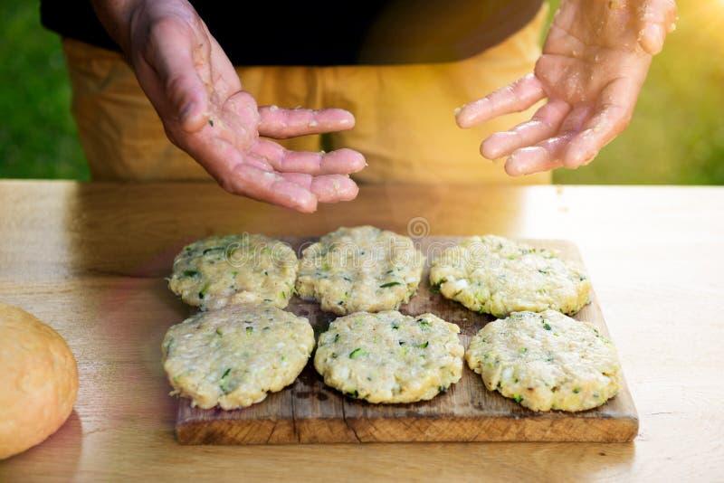 Smutsiga händer för manvisning, når att ha förberett kött- och zucchinihamburgare, trädgårds- matbegrepp för sommar royaltyfri fotografi