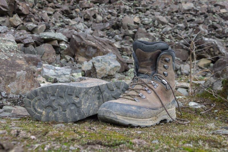 Smutsiga kängor för att fotvandra på stenar i skogen efter en vandring royaltyfria bilder