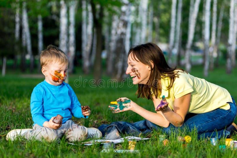 Smutsiga moder och son och målarfärg utomhus royaltyfri foto